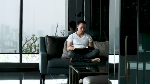 handsome asian man is reading book at the sofa after work in his home - magazine stock videos & royalty-free footage