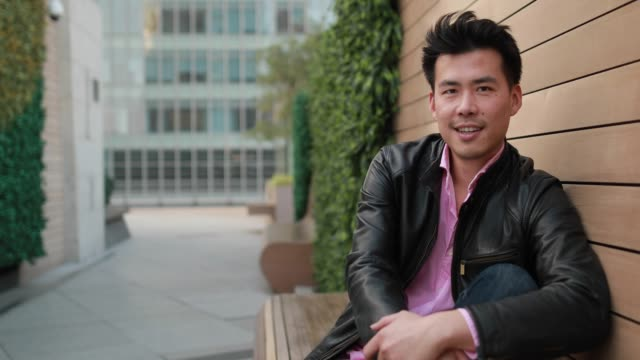 handsome asian man sitting on bench - handsome people stock videos & royalty-free footage