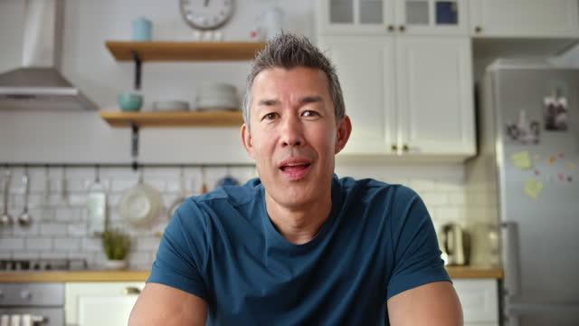 stockvideo's en b-roll-footage met ld knappe aziatische mens die op een videoconferentievraag van zijn huis spreekt - zitten