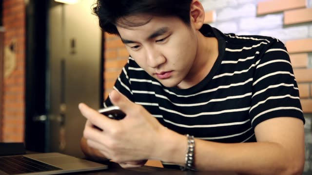 handsome asian young man busy on the smartphone at office table - dependency stock videos & royalty-free footage