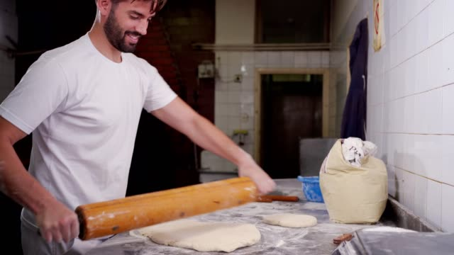 handsome baker rolling the dough - rolling pin stock videos & royalty-free footage
