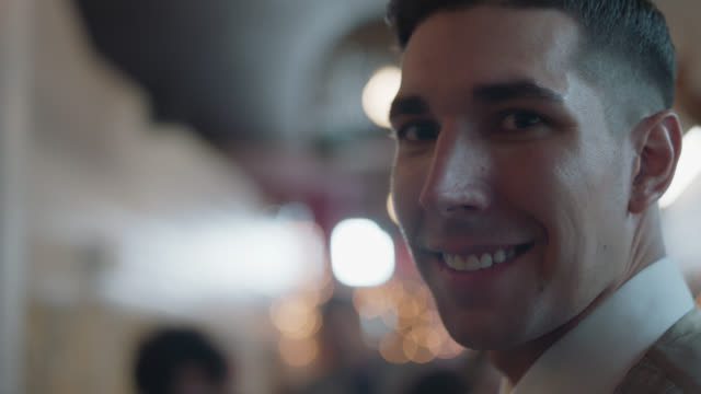 vidéos et rushes de cu. handsome bartender looks into the camera while he shakes a cocktail shaker - shaker