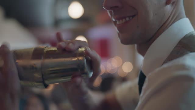 vidéos et rushes de cu. handsome bartender shakes a cocktail shaker while making a drink - shaker