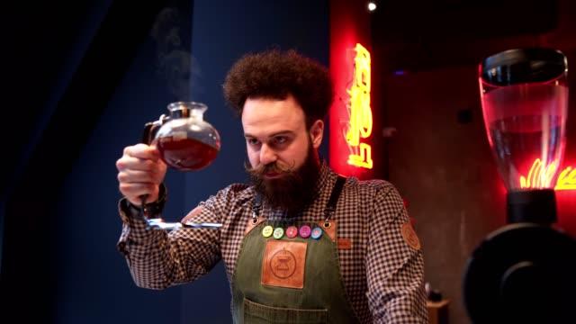 vídeos de stock, filmes e b-roll de barista barbudo considerável que prende uma bacia enchida com o café - barista