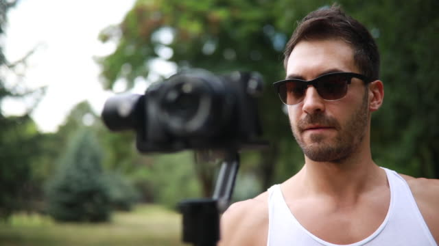 handsome bearded man filming with a camera - blogging stock videos & royalty-free footage