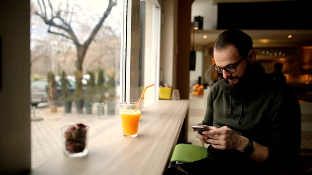 Handsome bearded man in the cafe using his mobile phone and enjoying healthy drinks