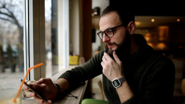 bärtiger mann das café mit seinem handy und genießen gesunde getränke - internet café stock-videos und b-roll-filmmaterial