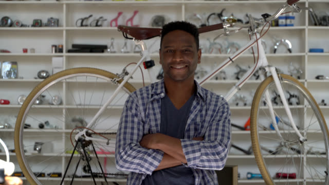 handsome black business owner of a bicycle shop looking at the camera smiling with arms crossed - entrepreneur stock videos & royalty-free footage