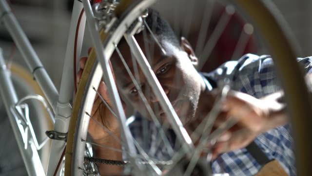 handsome black man adjusting the back wheel of a bicycle at a repair shop - aggiustare video stock e b–roll