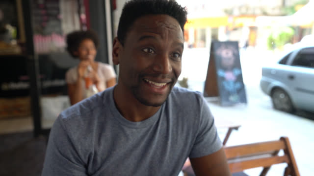 Handsome black man at a juice bar talking to someone very happy and smiling