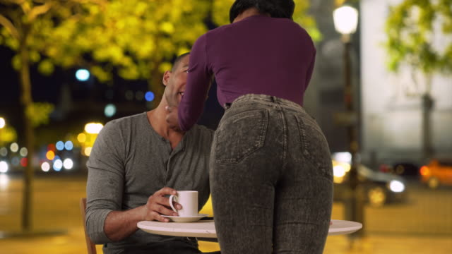 Handsome black man sitting at cafe enjoys flirtatious girlfriend's company