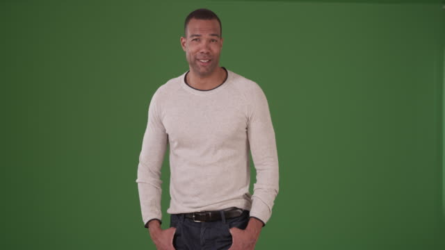 handsome black man smiling in a trendy white sweater on green screen - african american ethnicity stock videos & royalty-free footage
