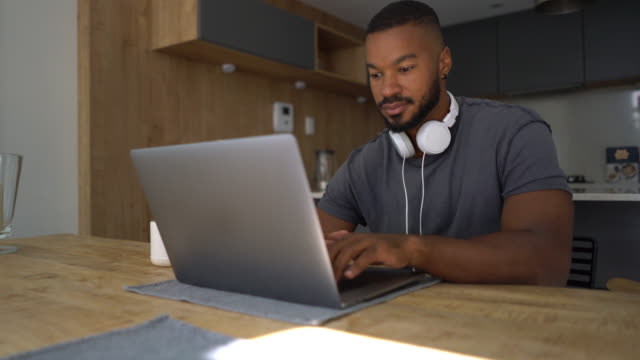 handsome black man working on his laptop wearing his headphones on neck looking focused - using laptop stock videos & royalty-free footage