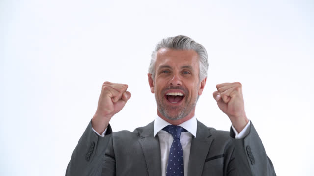 Handsome business man celebrating with arms raised and excited