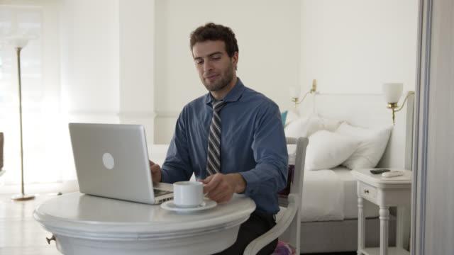 schöne geschäftsmann arbeiten auf laptop und kaffee genießen in seinem hotelzimmer - hotel stock-videos und b-roll-filmmaterial