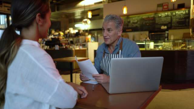 handsome business owner of a bakery interviewing a young woman - new hire stock videos & royalty-free footage