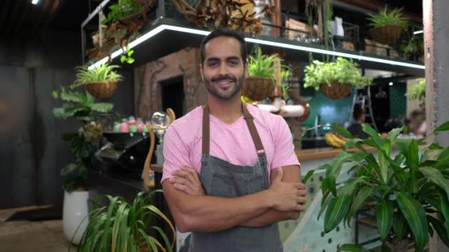 stockvideo's en b-roll-footage met knappe ondernemer van een kleine coffeeshop kijken camera glimlachen met armen gekruist - armen over elkaar