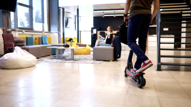handsome businessman entering the office on his scooter - motorino video stock e b–roll