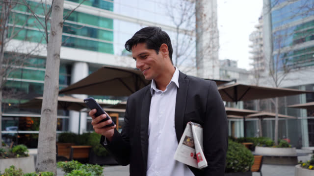 vídeos de stock e filmes b-roll de handsome businessman holding a newspaper under his arm while chatting very cheerfully on smartphone - jornal