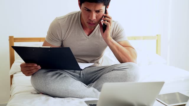 handsome businessman in his bed is making notes and smiling while working with a laptop at home - place of work stock videos & royalty-free footage