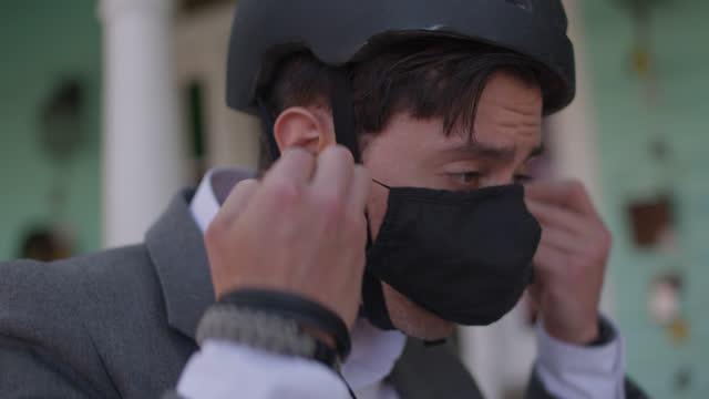 cu handsome businessman puts on bike helmet and protective face mask before biking to work - endast en man i 30 årsåldern bildbanksvideor och videomaterial från bakom kulisserna