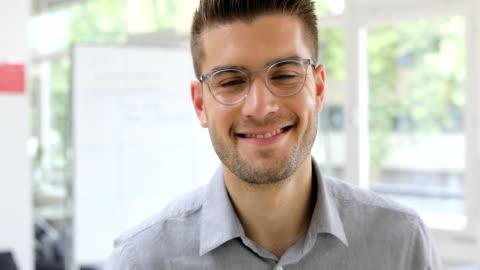 vídeos y material grabado en eventos de stock de apuesto hombre de negocios sonriendo en nueva oficina - de ascendencia europea