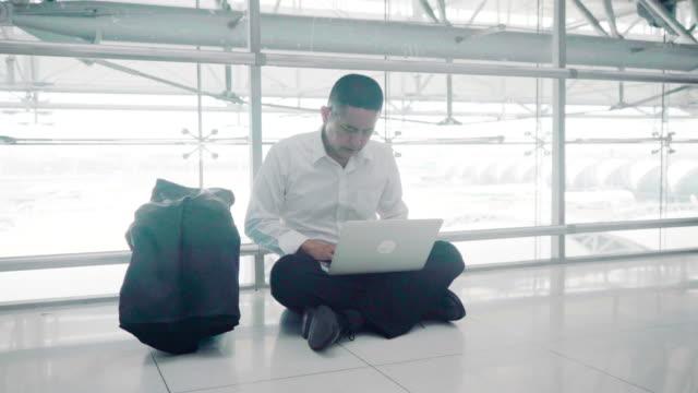 床にメールを送信するためにコンピュータを使用しながら、彼のラップトップを訴えるハンサムなビジネスマン - コンピュータハードウェア点の映像素材/bロール