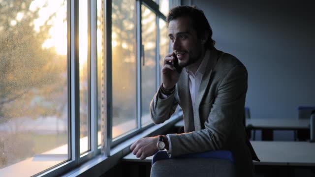 vidéos et rushes de homme d'affaires bel parlant sur le mobile dans le bureau - seulement des jeunes hommes