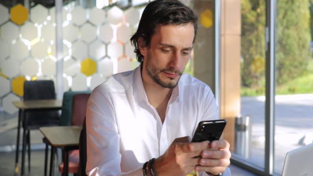 vidéos et rushes de homme d'affaires bel utilisant le téléphone dans le café - vêtement de peau