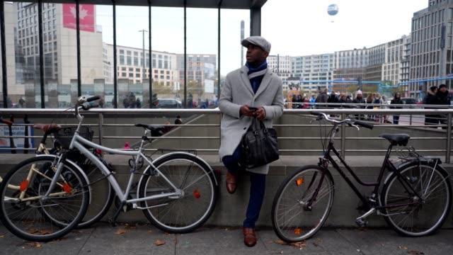 Gut aussehend Geschäftsmann warten, dass jemand an einen Fahrradständer