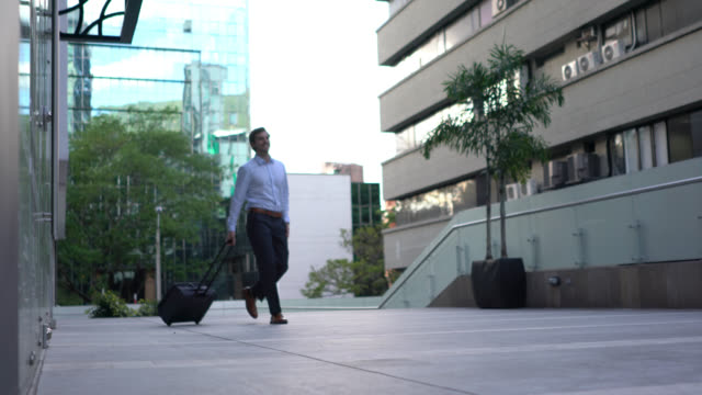 handsome businessman walking out of the hotel with his wheeled luggage - wheeled luggage stock videos and b-roll footage