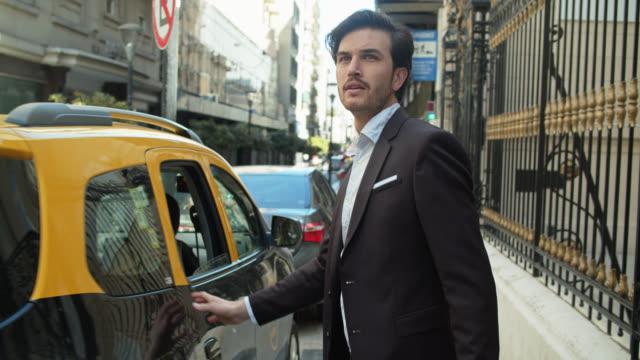 vídeos y material grabado en eventos de stock de guapos empresarios que salen del taxi en la calle buenos aires - handsome people