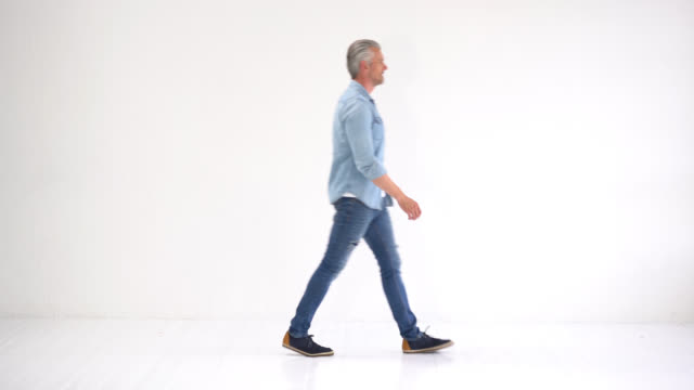 vídeos de stock e filmes b-roll de handsome casual man walking from one side to another - fundo branco