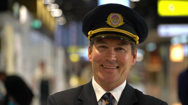 vídeos de stock e filmes b-roll de handsome caucasian airplane pilot at the airport facing camera smiling - tripulação