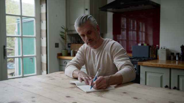 handsome caucasian man at home writing on his journal - handsome people stock videos & royalty-free footage