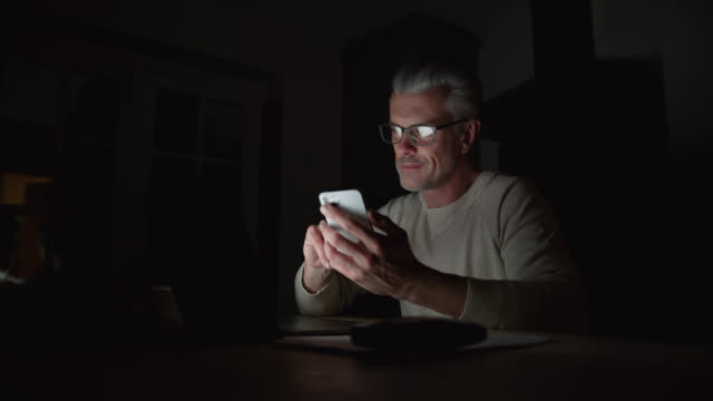 handsome caucasian man working late at night using his smartphone and laptop - urgency stock videos & royalty-free footage