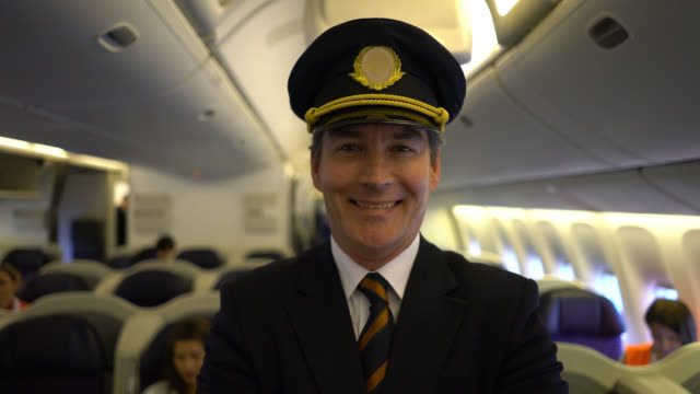 handsome caucasian pilot standing at the passenger cabin smiling at camera with arms crossed - pilot stock videos & royalty-free footage