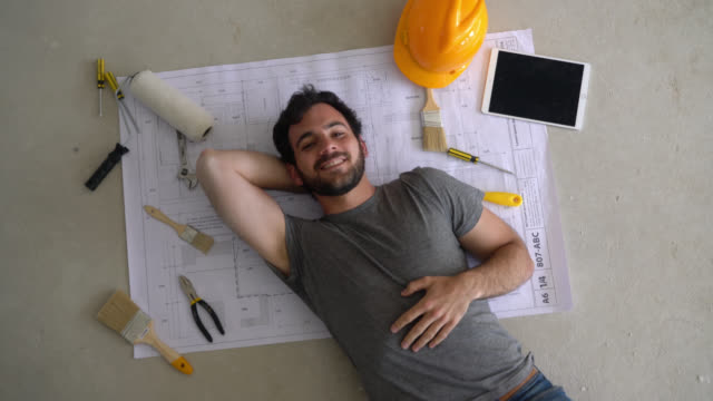 handsome constructor lying down on floor on top of a blueprint with tools and a tablet next to him smiling at camera - renovation stock videos & royalty-free footage