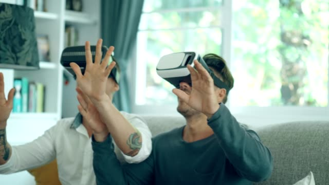 lgbt handsome couple enjoy playing virtual reality simulator for relaxation - cyberspace stock videos & royalty-free footage