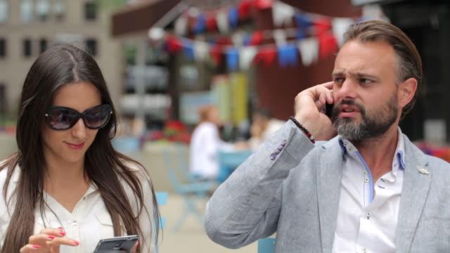 vídeos y material grabado en eventos de stock de pareja hermosa sentada en el café y el uso de teléfonos - estar colgado