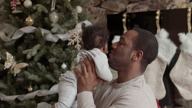 a handsome dad plays with his newborn daughter on christmas day - genderblend stock videos & royalty-free footage