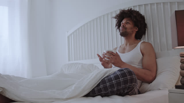 Handsome dark skinned man with afro hair in his forties laying back in white hotel bed enjoying me-time while drinking a cup of coffee on a day off - right in frame a bedside lamp.