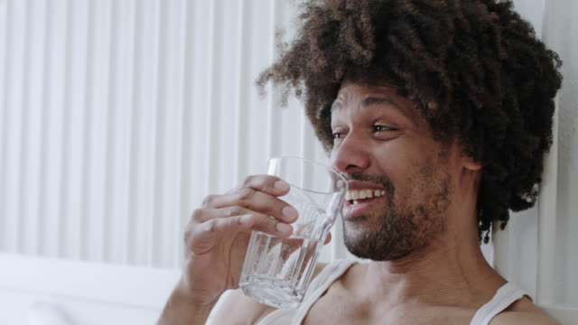 Handsome dark skinned man with afro hair in his forties sits on white hotel bed while enjoying himself, he drinks a glass of healthy mineral water.