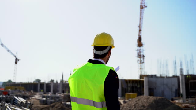 handsome  engineer wearing hardhat and holding blueprint at construction site - foreman stock videos & royalty-free footage