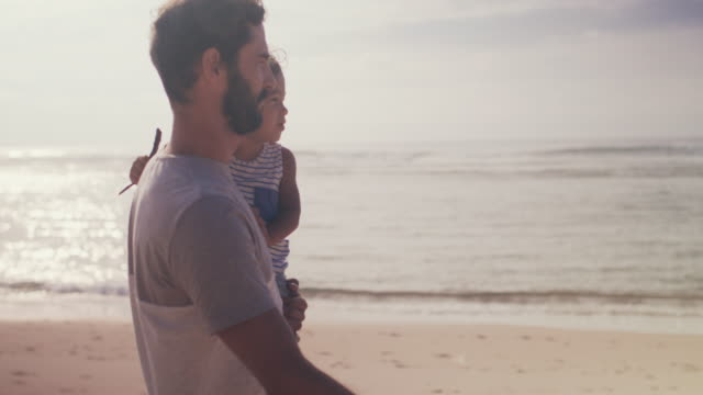 handsome father carrying beautiful baby boy on beach - single father stock videos & royalty-free footage