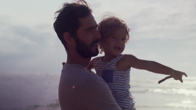 handsome father carrying beautiful, smiling baby boy on beach - picking up stock videos & royalty-free footage