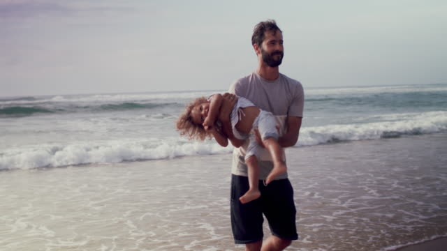 Handsome father spinning beautiful boy in his arms on beach