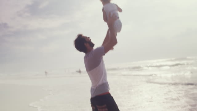 handsome father throwing boy into the air and catching him on beach - picking up stock videos & royalty-free footage
