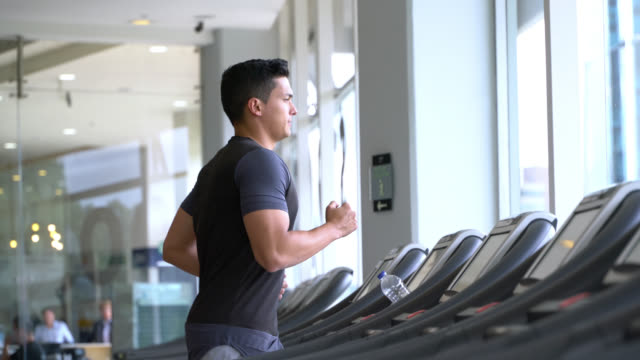 handsome fit man running on the treadmill - treadmill stock videos & royalty-free footage