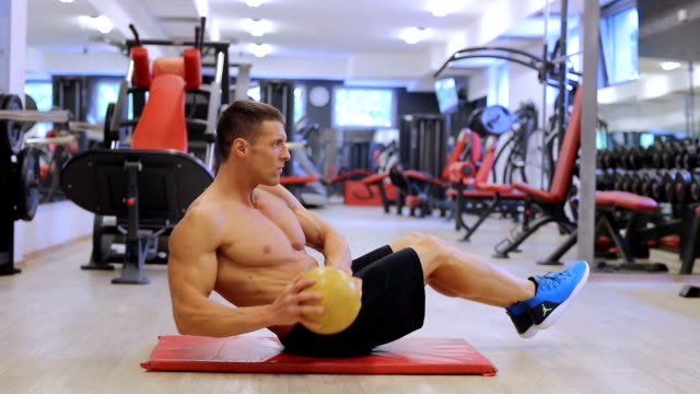 vídeos de stock e filmes b-roll de handsome fit sporty man does abdominal exercises in the gym - braço humano